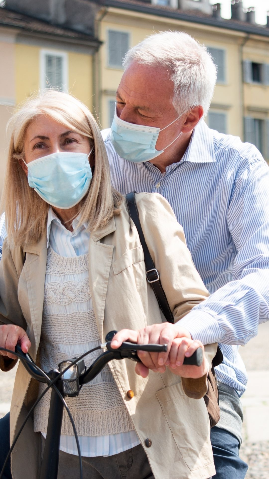 elderly couple with masks on an ebike
